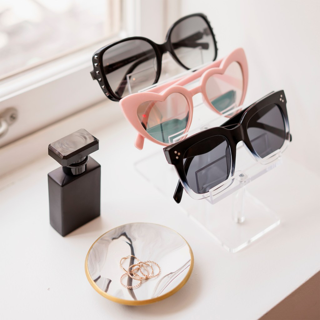 assorted sunglasses, black perfume, rings, ring dish, window. how to rock instagram on a budget.