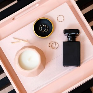 pink tray, candle, perfume, rings, ring holder, matches. black and pink pallet