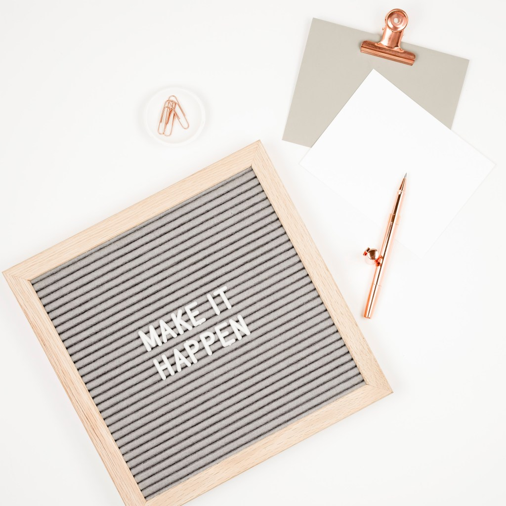 felt letter board that says make it happen. gold pen and paper clips, paper, paper clip holder.