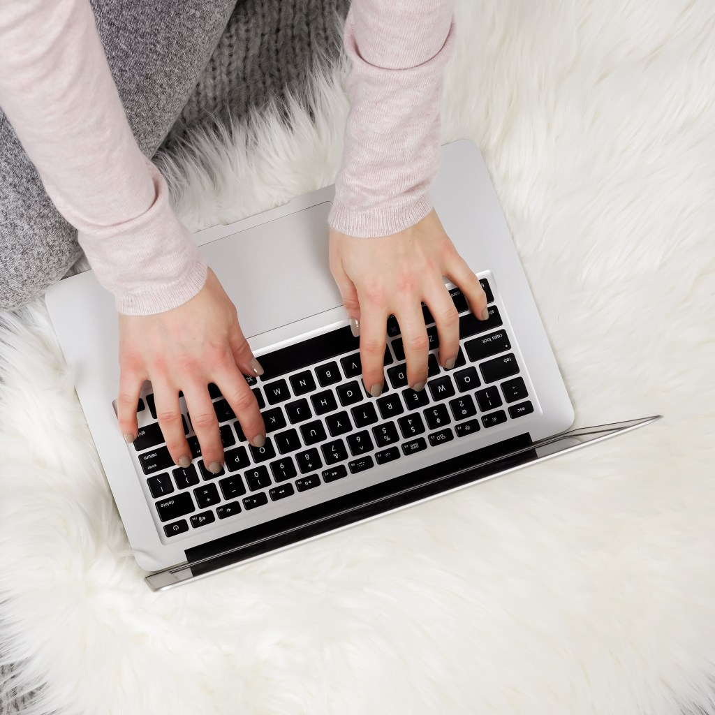 fur blanket, laptop, fingers on laptop. 5 reasons why you're not getting the blog traffic you want.