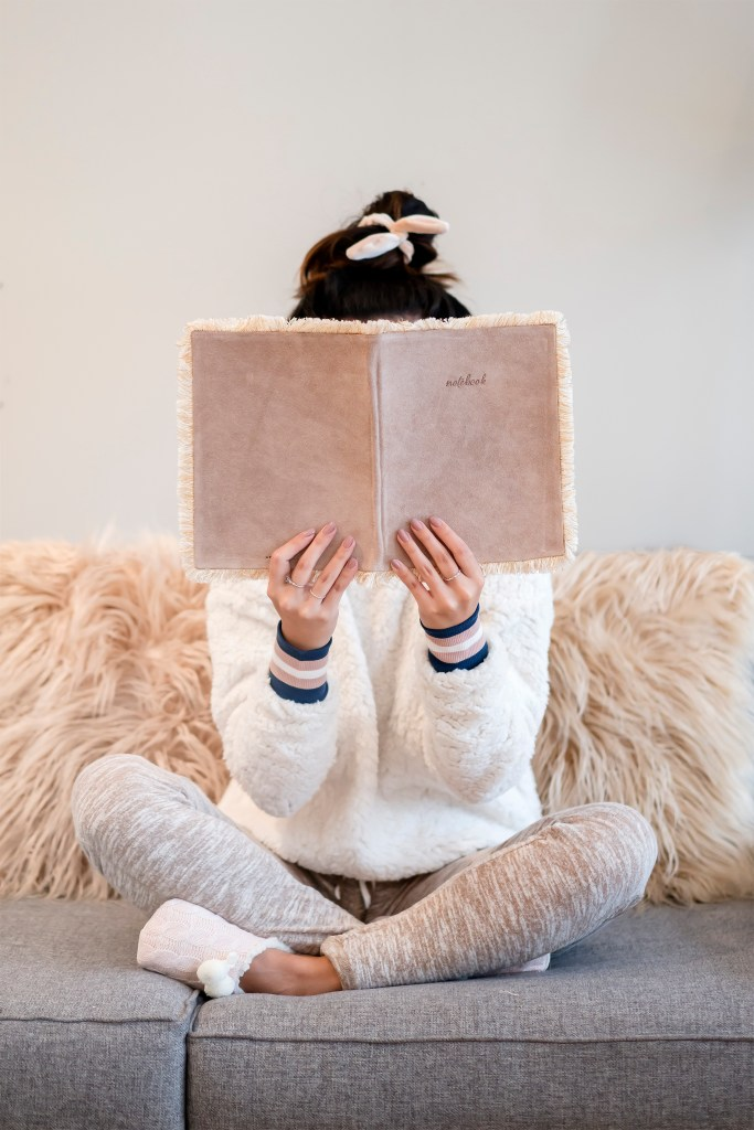 girl sitting on couch with furry blanket and comfy clothes, notebook reading. hair in bun with scrunchie. Turning Off: 5 Ways Bloggers can Unplug and Recharge