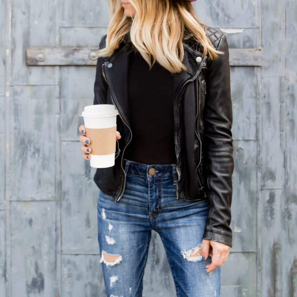 blonde woman in leather jacket, ripped jeans, and holding a takeaway coffee. 25 bad-ass things to do this year