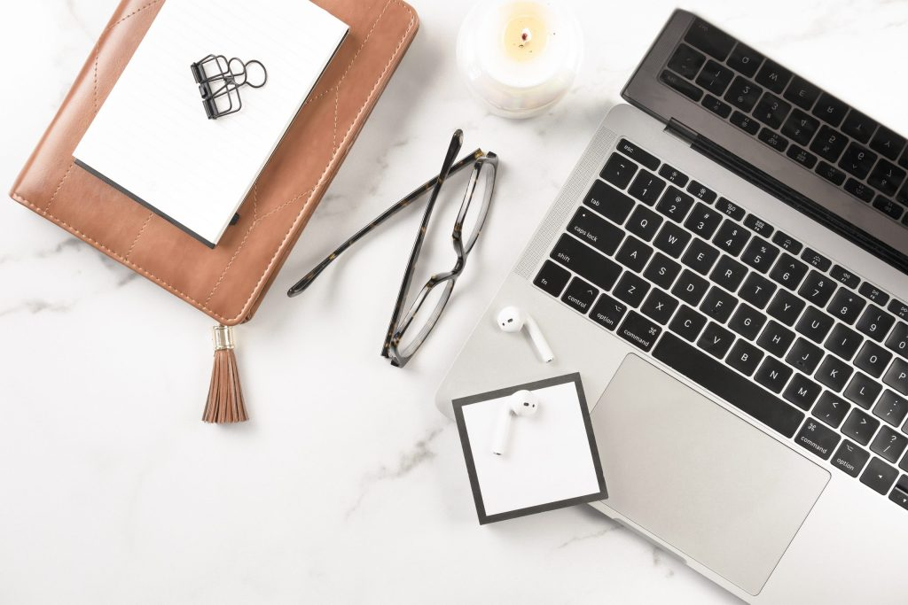 macbook, leather notebook, glasses, airpods. marble desk setup. candle. how to use twitter to boost your blog traffic