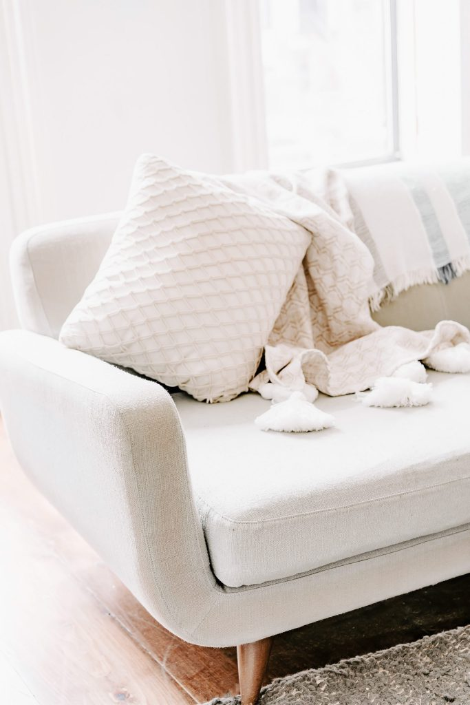 white couch, white blanket, white pillows. bright and airy. 10 things every girl should have on her spring cleaning list.