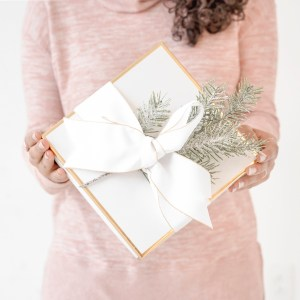 woman in pink sweater holding white and gold present. the ultimate gift guide for her.