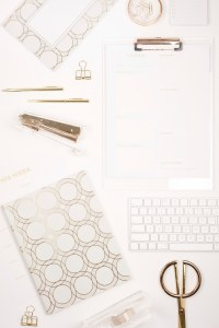get planning. gold and white flat lay. gold scissors, stapler, paperclips, pen, keyboard. 5 things you can schedule to make blogging that much easier