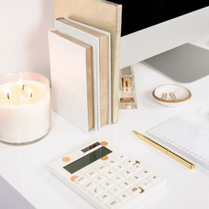 candle, computer, books, calculator, desk flatlay. the two secrets that will help you slay your goals