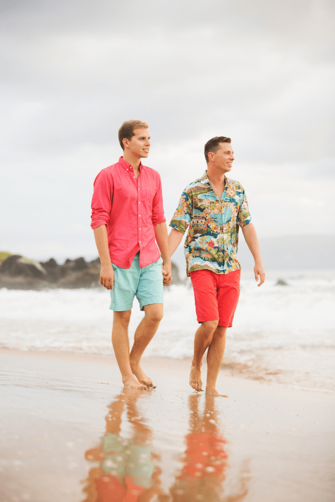 same sex couple on a beach, walking in the sand holding hands.