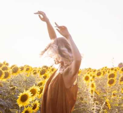 woman twirling around in sunflowers