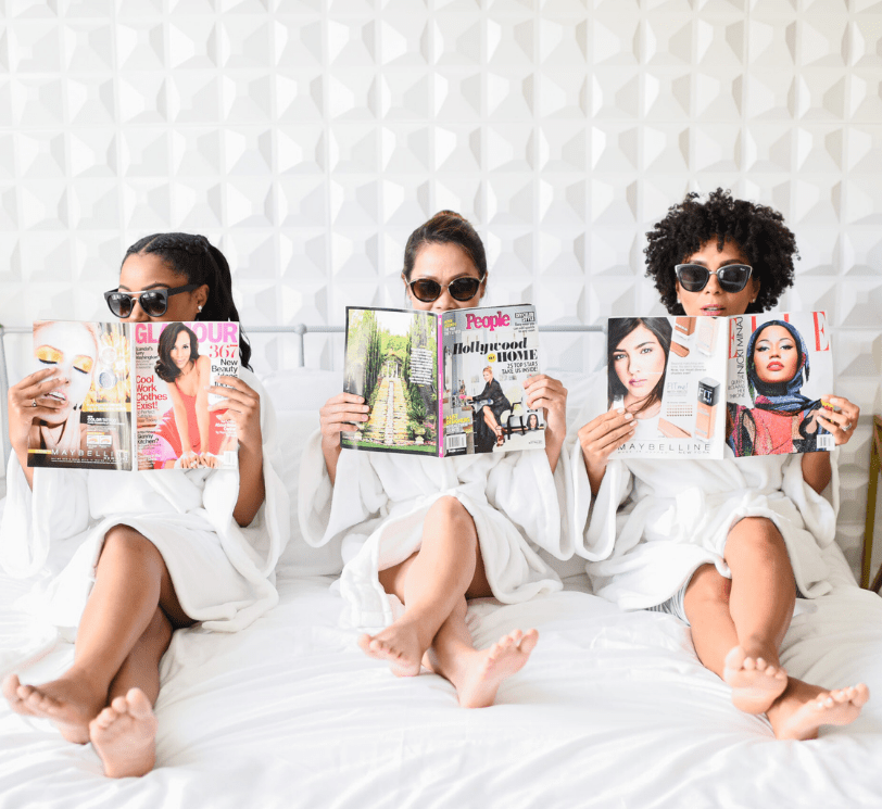 women sitting on the bed in bathrobes wearing sunglasses and reading magazines