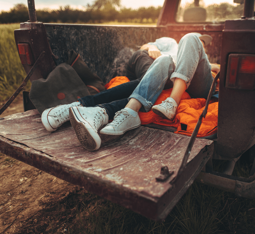 boy and girl lying in back of pickup truck