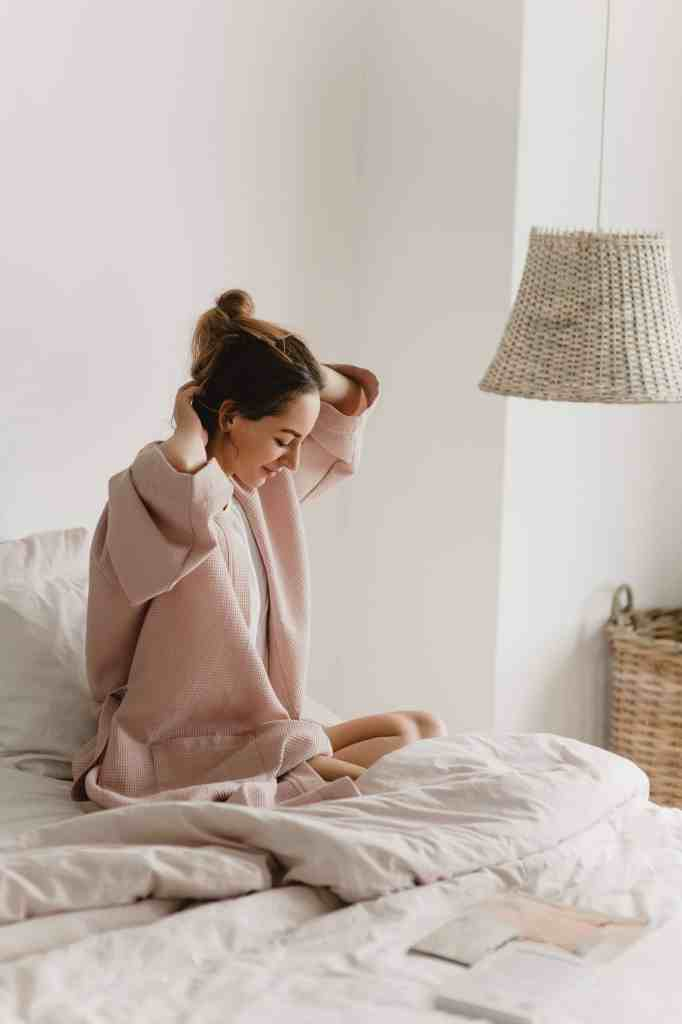 girl putting up her hair, in bed, wearing pink sweater. wicker basket in background. How to Live a More Intentional Life: 23 Ideas to Inspire You