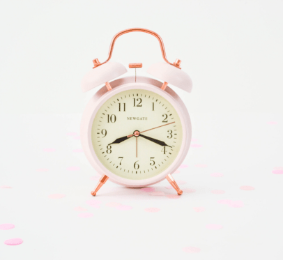 pink alarm clock with pink confetti lying around. wasting your time on