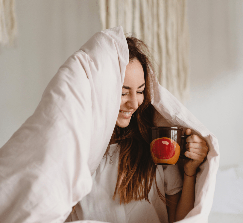 woman in blanket with cup of tea
