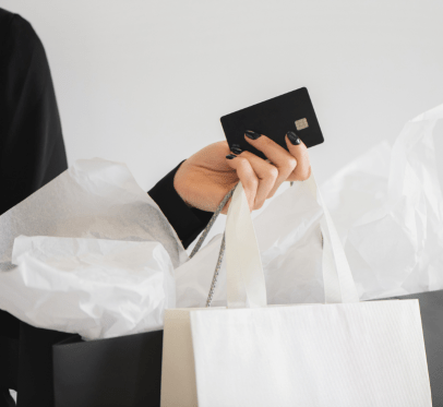 woman holding shopping bags and credit card. important questions to ask yourself before you splurge