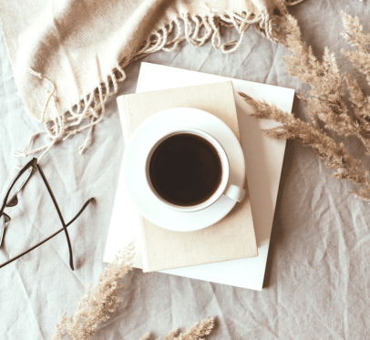 HOW USING THE FIVE MINUTE JOURNAL ACTUALLY IMPROVED MY MINDSET. stack of notebooks with a cup of coffee on top. glasses, pampass grass and blankets in the background
