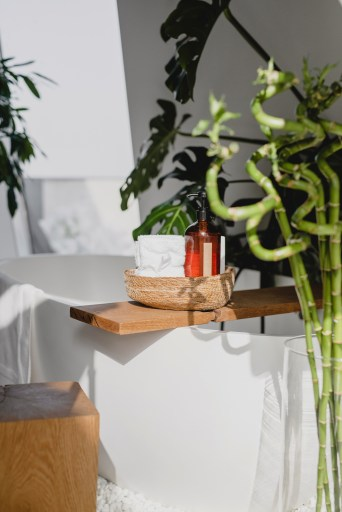 11 WAYS TO BE KINDER TO YOUR BODY. bathtub with bamboo surrounding it, bath tray with bodywash and towels sitting on top.