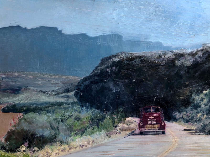 Antique red truck coming around the bend near, a big black rock behind on a misty morning.