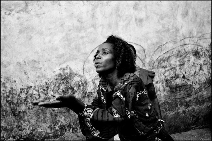 Dans les années 80 une jeune fille quitte Benin City dans le Sud du Nigéria pour fuir la pauvreté. Elle en revient riche 10 ans après. Elle s'est prostitué en Europe. En rentrant elle crée un reseau et commence à envoyer les filles du village en Italie, en Espagne ou en France. Elles partent volontairement ou sous la pression de leurs familles qui voient la dedans un moyen de subsistance. Le sujet n'est pas tabou, les familles posent facilement avec la photo du membre qui se prostitue en Europe et qui envoie de l'argent pour la construction de la maison chaque mois. Ce qui est tabou en revanche c'est que les reseaux font faire un pacte vaudou avec la complicité de pretres qui prelevent leurs dimes au passage. Ce pacte dure de 3 jours à Une semaine. A la fin du pacte la fille promet de rembourser les 50000 euros ' du passage'  et de ne jamais parler du Pacte. Après le Pacte, les filles partent souvent par leurs propres moyens vers l'Europe. Là bas elles retrouvent le reseau qui les mettront sur nos trotoirs. /// LE PACTE