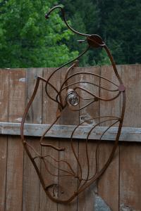 a patina metal face sculpture, wall mount piece of work by artist, designer and inventor John Czegledi