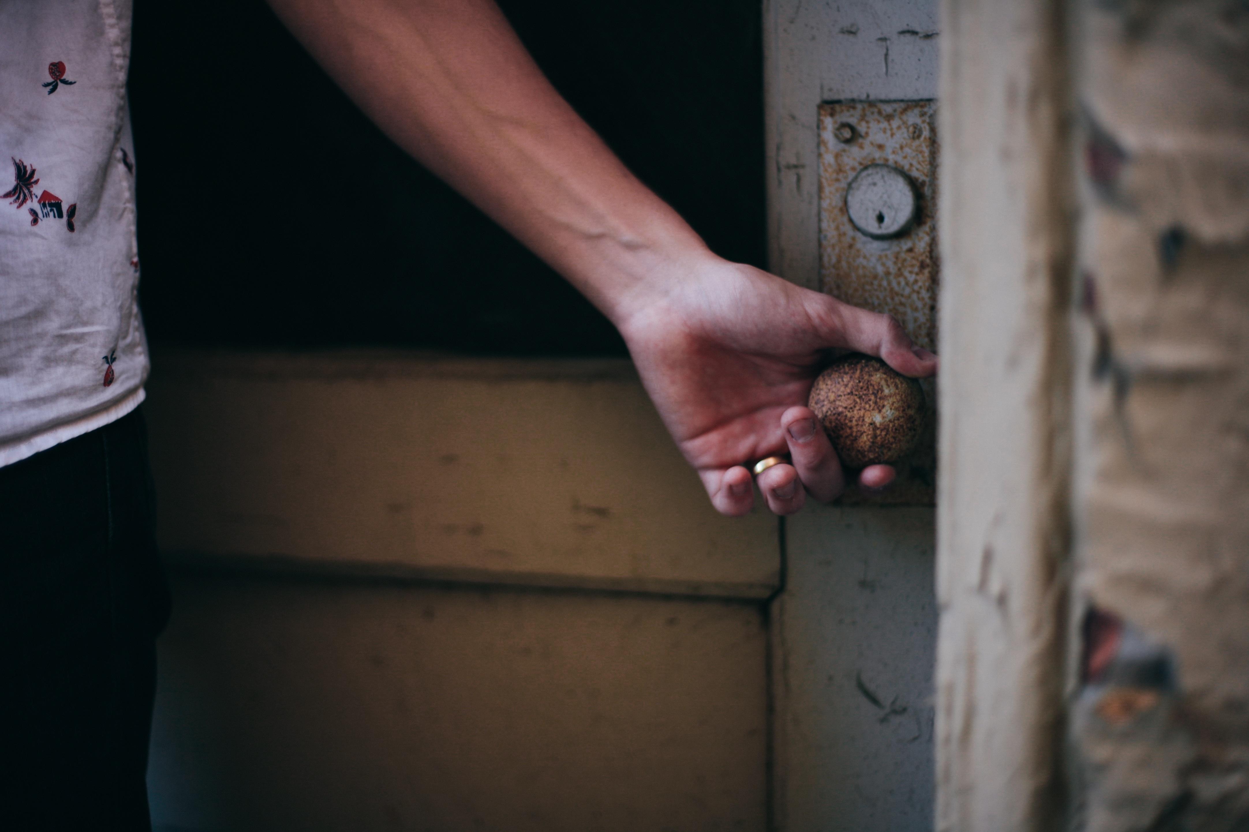 Zdjęcie przedstawiające osobę otwierającą mocno zdewastowane drzwi