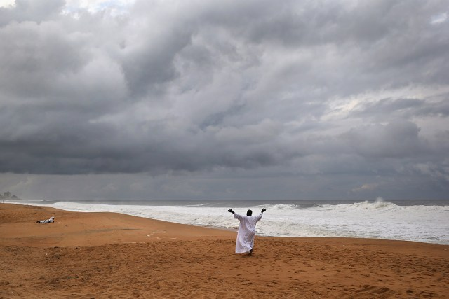A member of the Church of Aladura prays for God to rescue Liberia from Ebola, on the beach in Monrovia