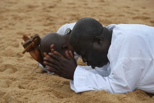 Two men pray on the beach in Monrovia, calling for God to help Liberia during the current Ebola crisis