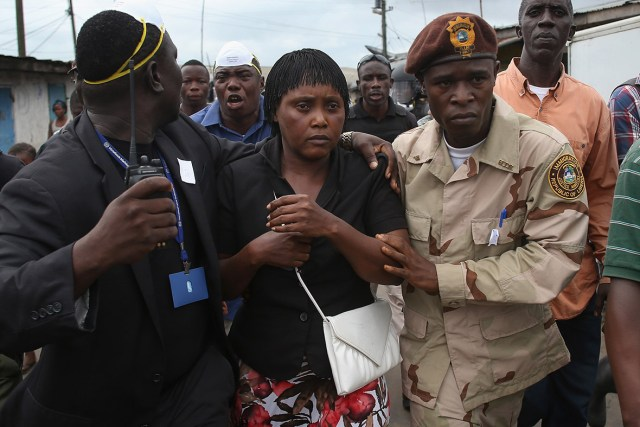 West Point Commissioner Miata Flowers is escorted out of the slum by members of Liberia's Ebola Task Force. The military was called in to extract the commissioner and her family from the seaside slum after residents blamed the government for planning a holding centre for suspected Ebola patients in their community