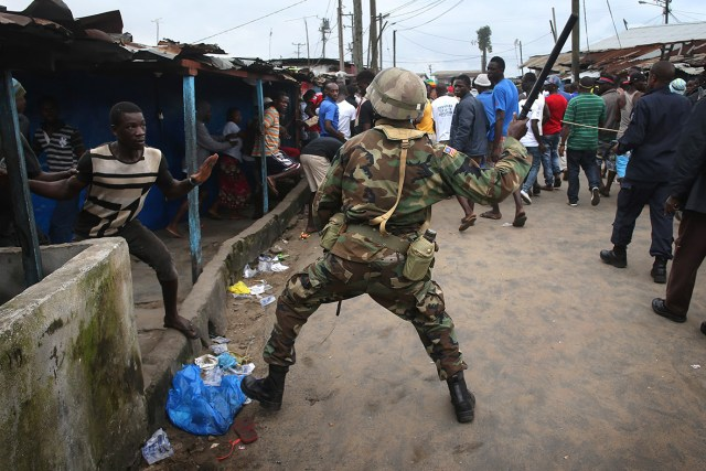 A Liberian Army soldier, part of the Ebola Task Force, beats a local resident while enforcing a quarantine on the West Point slum. The government ordered the quarantine of West Point, a congested seaside slum of 75,000, in an effort to stop the spread of the virus in the capital