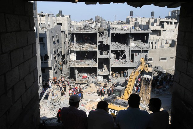 Palestinians watch as rescue workers search for victims under the rubble of a house destroyed in an Israeli air strike that killed three senior Hamas military commanders in Rafah