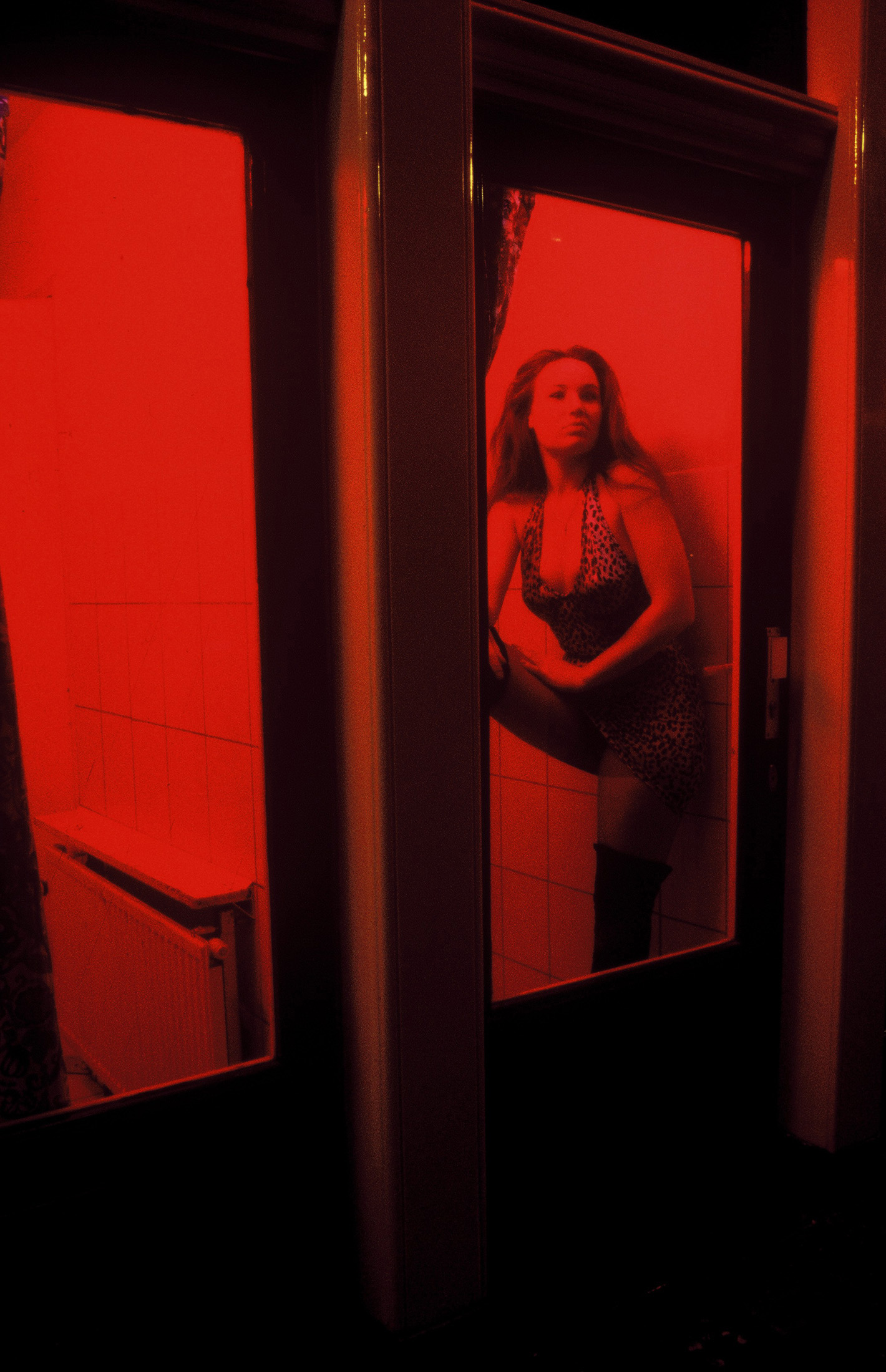 A Dutch prostitute sits behind her window in the red light district in Amsterdam, The Netherlands