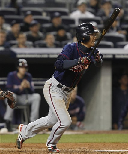 Minnesota Twins ' Tsuyoshi Nishioka hits an eighth-inning infield single that bounced off the glove of New York Yankees pitcher Rafael Soriano in the Twins' 4-3 loss to the Yankees in their baseball game at Yankee Stadium in New York, Monday, April 4, 2011.