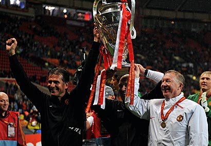 Manchester United manager Sir Alex Ferguson (R) and assistant Carlos Queiroz hold the trophy after the UEFA Champions League final May 21.
