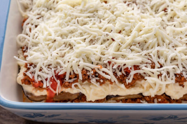 Image of unbaked keto eggplant lasagna showing individual layers of eggplant, ricotta cheese, meat sauce and mozzarella cheese topping.