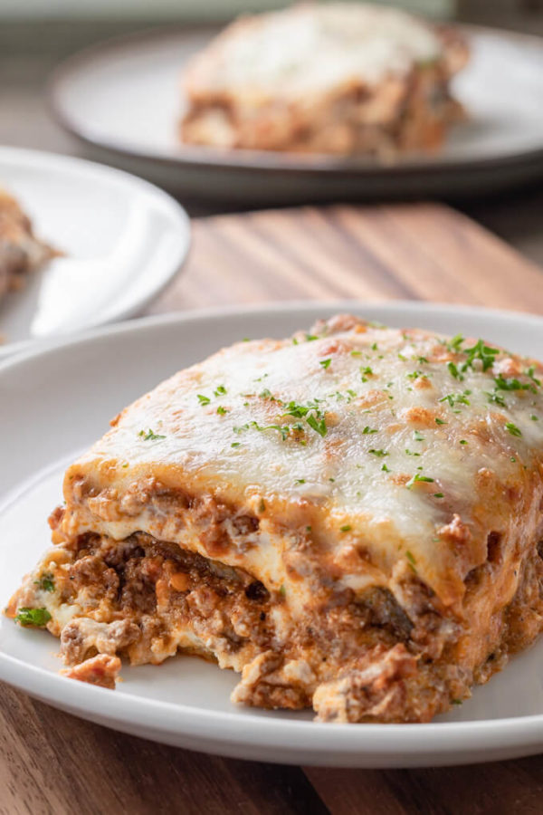 Slice of eggplant lasagna with meat sauce topped with chopped parsley on a white plate.