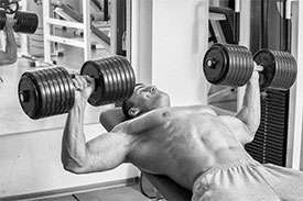A muscular man bench pressing heavy dumbbells.