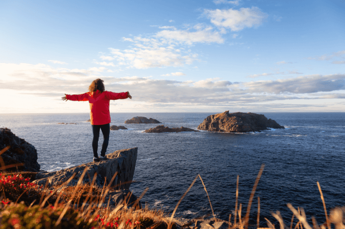 woman standing on cliff in newfoundland and labrador