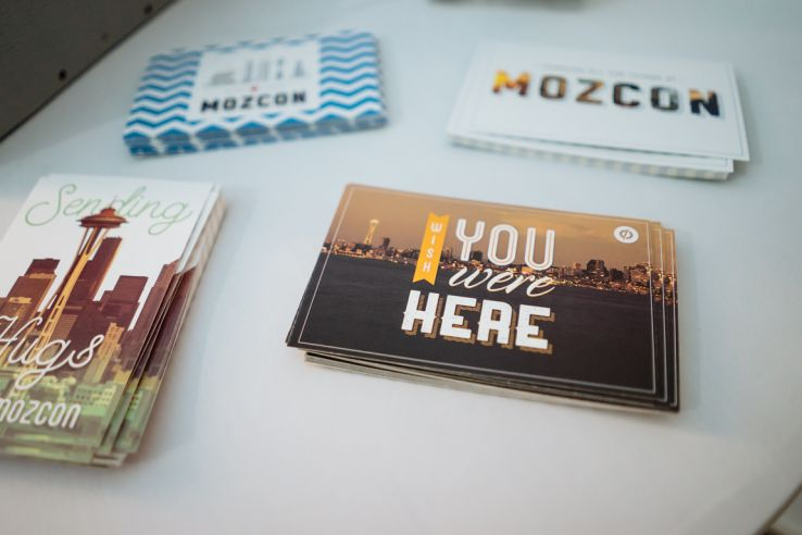 "Postcards sitting on a table from a MozCon in the past; they say ""MozCon"" and ""Wish You Were Here"""