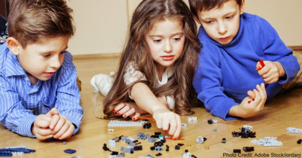 funny cute children playing lego at home, boys and girl smiling, first education role