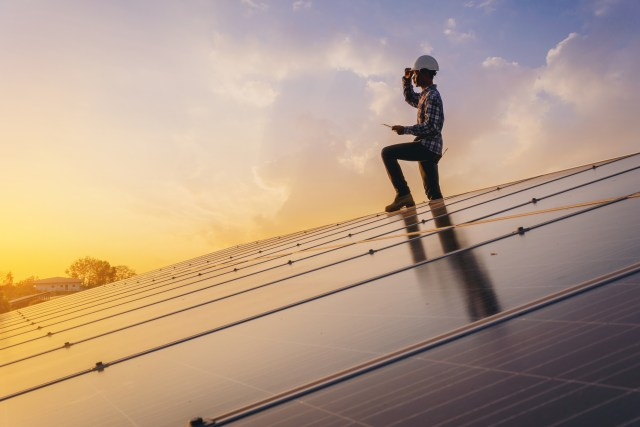 Man in construction hat, standing on top of a roof covered in solar panels, thinking about solar energy savings.