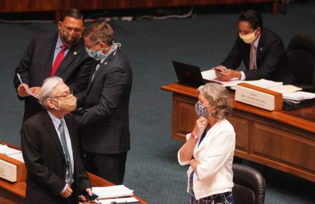 Right, Senator Laura Thielen shares a conversation with left, Les Ihara. Background left, Senator Kurt Fevella chats with Senator Gil Riviere before the floor session begins at the Capitol. July 6, 2020