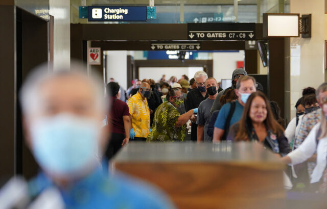 Hundreds of passengers arrive and wait in a line with Governor Ige in foreground during press conference. Arriving passengers are screened if they have pre-travel testing required to avoid the 14-day traveler quarantine. Tests are only accepted from trusted testing and travel partners. October 15, 2020