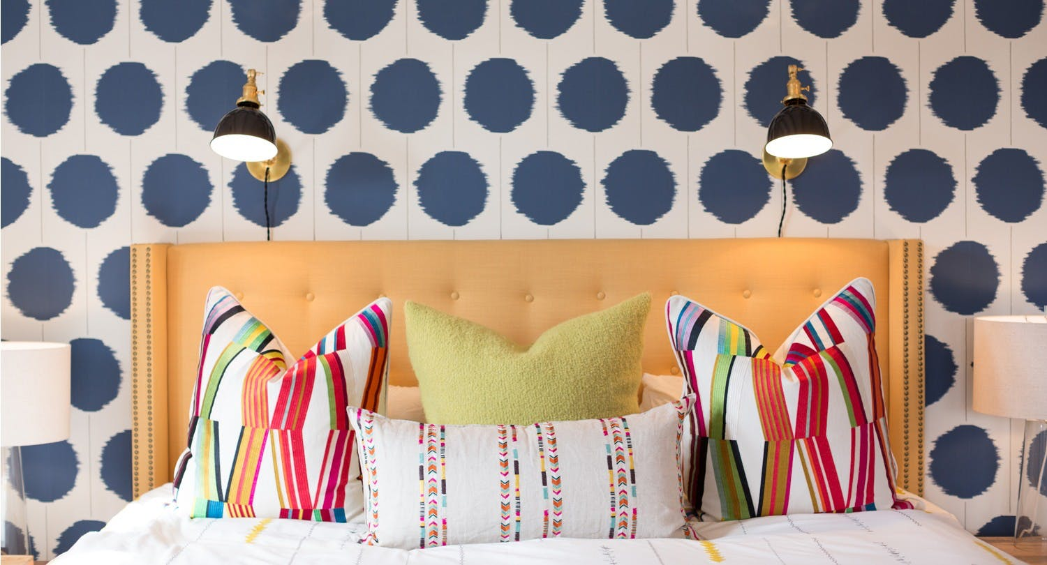 A vibrant bed sets off this super interesting wall paper choice