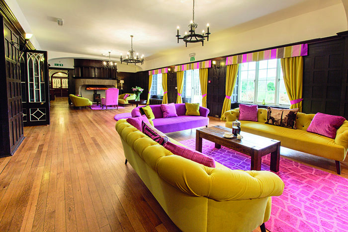 Sitting room at Achnagairn Castle, with mustard and purple velvet armchairs and sofas