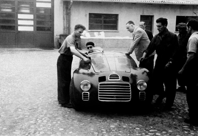 "Enzo Ferrari with the 125 S in the Factory courtyard. At the wheel is Ferdinando ""Nando"" Righetti."