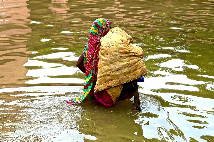 A woman makes her way through knee-deep flood waters. Credit: Eklavya Prasad