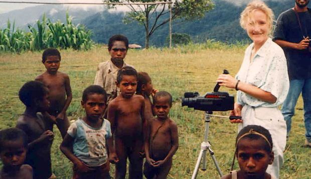 Old photograph of woman videotaping young children in the wilderness