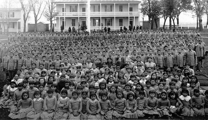 Black-and-white photo of Native American children and boarding school.