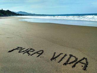 """The motto of Costa Rica """"Pura Vida"""" written into the sand"""