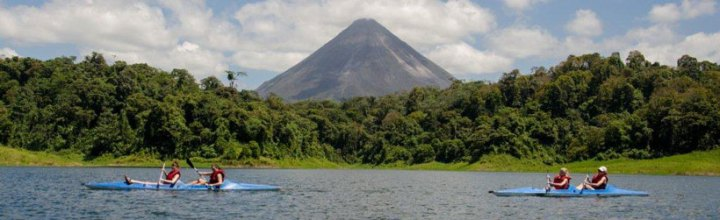 A pair of kayaking couples enjoying the spectacular view of the volcano from Lake Arenal